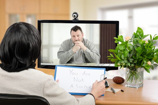 Man talks with psychotherapist via online video chat. He looking depressed. Black-haired psychiatrist holds written message for him - You are not alone. Horizontal shot indoors