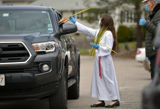 Altar server, Santina MacGregor, hands out palms and prayer cards to a parishioners on Sunday, April 5, 2020 at Our Lady of Mount Carmel and Our Lady of Loreto Church in Worcester, Mass.