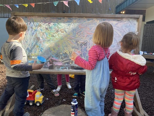 Children paint outside as part of their day at Small Wonders, a child care center in Portland, Oregon. The center has closed both of its schools in reaction to the global coronavirus outbreak.