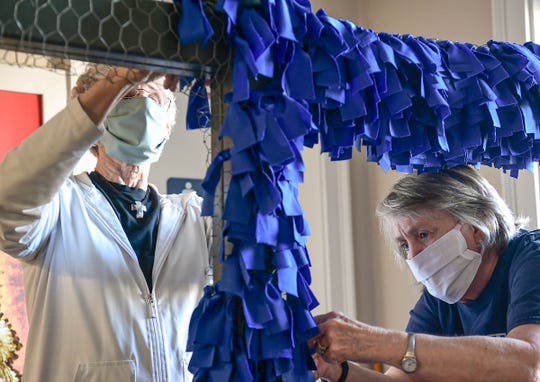 Sarah Crowder, right, and Pat Smith of St. John's United Methodist Church decorate a cross with blue ribbons before Maundy Thursday in the fellowship hall in Anderson Monday. Crowder said the cross is called the Covid-19 Cross of Hope, with a royal blue ribbon for each diagnosed person in South Carolina.  The idea started when there were 450 cases, but as the two prepare for placing the cross in front of the church Thursday morning, the cases rose above 2,000. Maundy Thursday is the Christian holy day falling on the Thursday before Easter. It commemorates the Washing of the Feet and Last Supper of Jesus Christ with the Apostles, as described in the canonical gospels.
