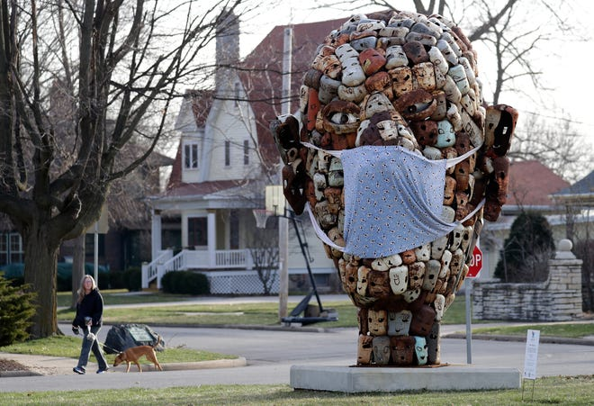 """A woman looks at a giant protective mask that someone placed on """"The Collective,"""" a sculpture by Paul Bobrowitz, along East College Avenue Monday, April 6, 2020, in Appleton, Wis."""