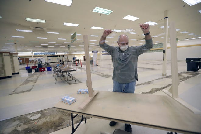 Todd Stevenson, chairman of Neenah's election task force, sets up a Plexiglas barrier to separate poll workers and voters in advance of Tuesday's election at the former Neenah Shopko store, 699 S. Green Bay Road. The building will serve as the city's sole polling place.