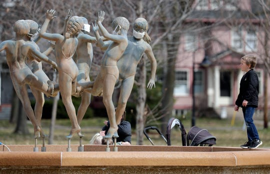 """Parker Coumbe, 6, of Appleton investigates the """"Ring Dance"""" sculpture that is covered with protective masks at City Park Monday, April 6, 2020, in Appleton, Wis. Parker was at the park with his mother, Kayla Coumbe."""