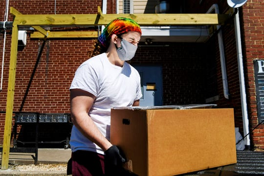 Trace Rudolph, a community intern at Haywood Street Congregation, closes his eyes as the sun is reflected off a food container as he unloads boxes of food donated by Angela and Bryan King of 12 Bones April 4, 2020 in Asheville.