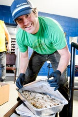 Bryan King opens a pan of catfish as he unloads food for the Welcome Table at Haywood Street Congregation April 4, 2020.