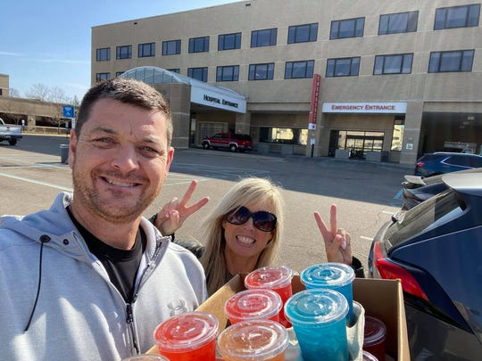 Ken and Kristen VanDalsen, owners of Epic Nutrition Smoothie Bar in Battle Creek and VIP Nutrition Smoothie Bar in Marshall deliver tea bombs donated to Bronson healthcare workers in Battle Creek, Mich., on March 25, 2020.