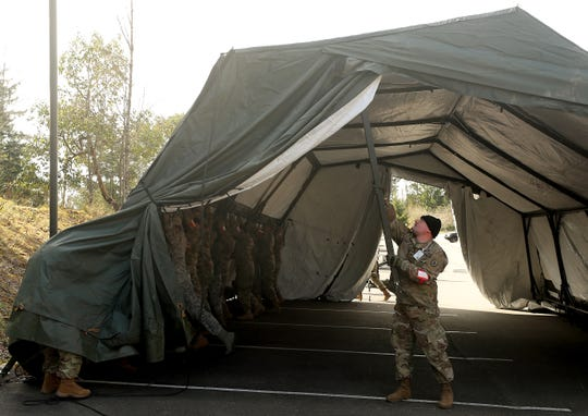 National Guardsman Daniel Abbott helps breakdown a tent as he and fellow guardsman swap out the tent for a smaller one while setting up for Kitsap County's first drive-up COVID-19 testing site at the Army National Guard Base in Bremerton on Sunday, April 5, 2020.