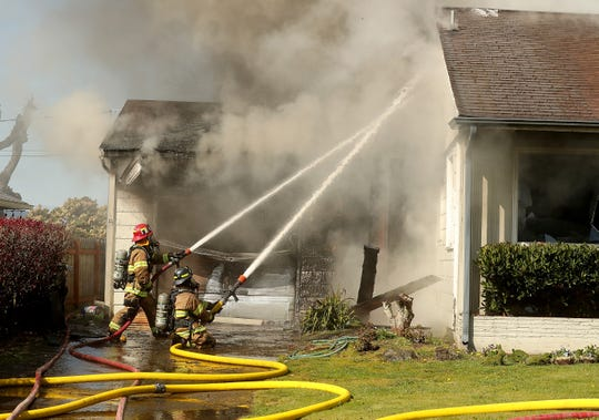 Bremerton firefighters extinguish a residential structure fire on Nipsic in Manette on Monday, April 6, 2020.