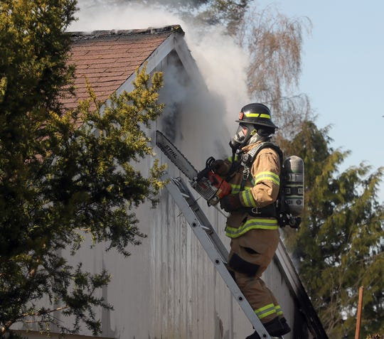 Bremerton firefighter/paramedic Rich Railsback uses a chainsaw to cut into the roof gable of a home to gain access to fire in the attic as Bremerton and Central Kitsap firefighters extinguish a residential structure fire on Nipsic in Manette on Monday.