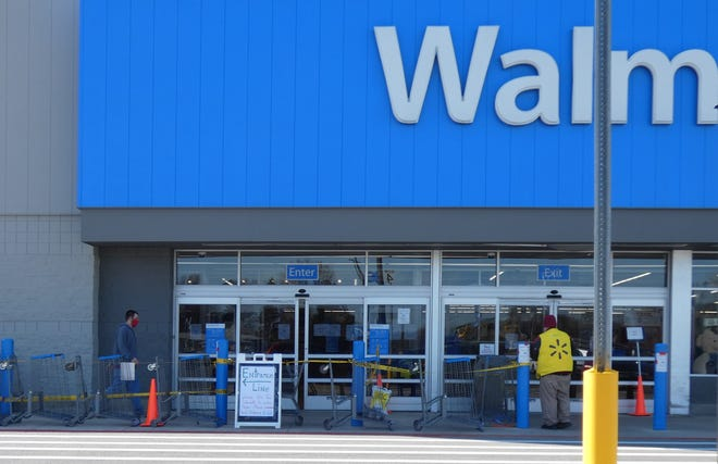 A sign in front of the Bucyrus Walmart store on Monday directs shoppers toward an entrance line along the front of the store.