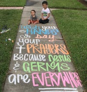 Brothers Brooks, 9 months, and Kyson, 5, Breland take a photo in front of their home. Their mom, Becca Breland, has been writing inspirational chalk messages in front of their home in Lamar Park.