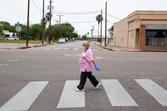 A women wearing a face-mask and gloves walks up Leopard Street on Monday, April 6, 2020.