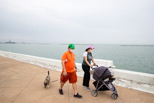 People wearing face-masks walk along the seawall on North Shoreline Boulevard on Monday, April 6, 2020.
