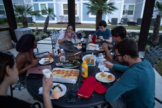 A group of students few still living in campus apartments since the COVID-19 outbreak started eat dinner in the court yard at Momentum Village campus housing on Friday, April 3, 2020.