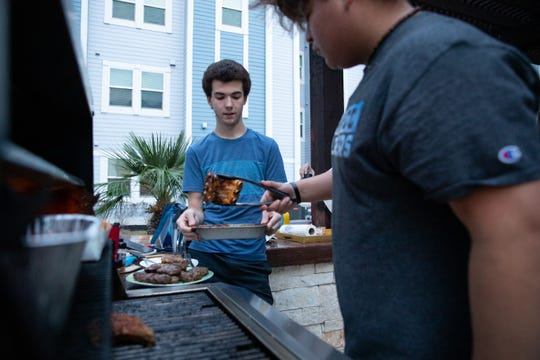 Texas A&M University-Corpus Christi freshmen Cade Hickman (left) helps cook dinner the court yard at Momentum Village campus housing on Friday, April 3, 2020. The small group of students are some of there few still living in campus apartments since the COVID-19 outbreak started.