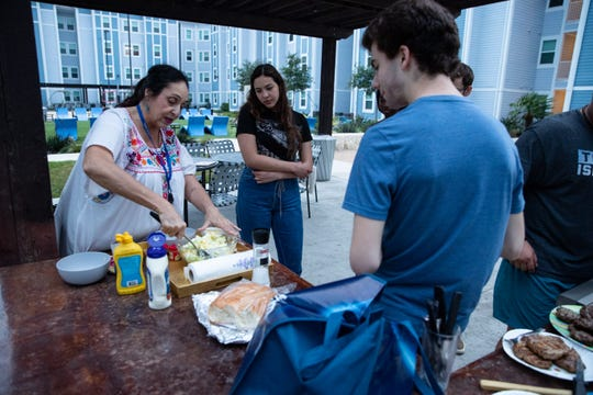 Texas A&M University-Corpus Christi graduate student Norena Gutierrez shows a group of undergrad students how to make her potato salad in the court yard at Momentum Village campus housing on Friday, April 3, 2020. The small group of students are some of there few still living in campus apartments since the COVID-19 outbreak started.