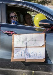 Amy Bryan blows on a noisemaker during a birthday parade for Jayden Noble on his 16th birthday.