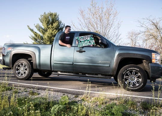 Hayden Carroll hangs out the window of a truck and yells happy birthday to Jayden Noble through the newly developed birthday parades.