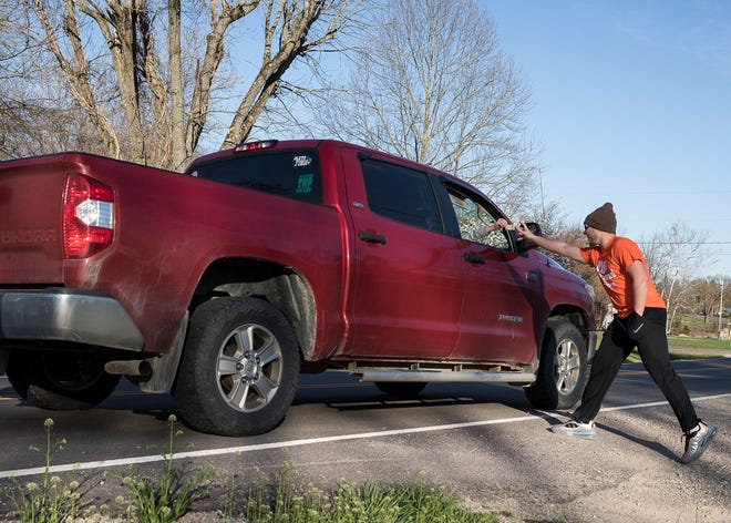 Huntington student Jayden Noble receives money for his birthday from a moving truck on Thursday, April 2, 2020. Noble, who turned 16, was not able to celebrate his birthday like years past with gatherings and friends and families due to the social restrictions caused by the coronavirus. To help with this, a birthday parade of vehicles stopped by his house with those honking and yelling happy birthday.