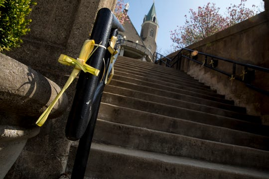 Palms hang on the hand railing at the Mt Adams Steps on Monday, April 6, 2020. Due to the new coronavirus pandemic, the annual Praying of the Steps has been canceled.