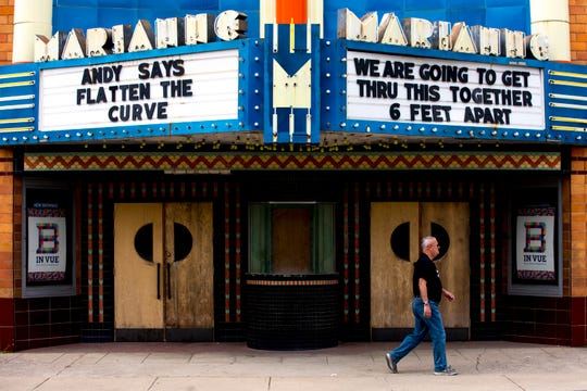 A man walks past the Marianne Theatre, which has signs promoting social distancing and flattening the curve displayed, on Monday, April 6, 2020, in Bellevue, Ky.
