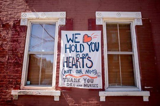 "A sheet with the words, ""We hold you in our hearts (not our arms)"" is displayed on a home on Bakewell Street in Covington, Kentucky on Thursday, April 2, 2020."