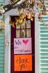 Signs thanking essential workers are displayed on a home on Philadelphia Street in Covington, Kentucky on Thursday, April 2, 2020.