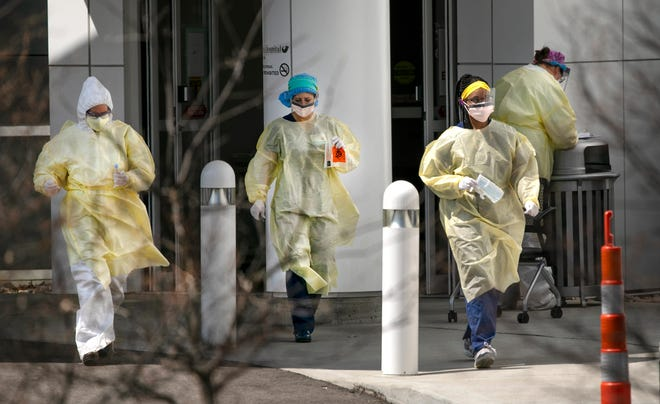 Jewish Hospital workers prepare for testing at the drive-thru location along Kenwood Road, Monday, April 6, 2020. Hospital workers are taking extra precautions during the new coronavirus pandemic. Anyone going through the site must have a doctor's order and an appointment.