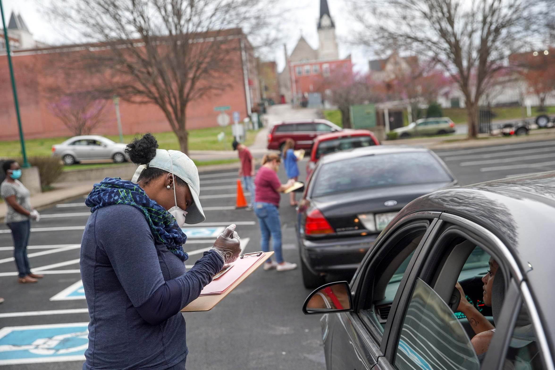 Kelsea Combs takes down a family's order for food distribution from Urban Ministries at Madison Street United Methodist Church in Clarksville, Tenn., on Friday, March 27, 2020.