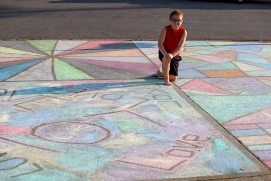 Zayden Iafelice, 8, kneels in the middle of four squares the Iafelice family decorated with chalk art in their driveway on Cyprus Court in Clarksville, Tenn., on Sunday, April 5, 2020.