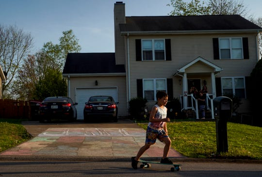 Alan Santana, 7, pushes off on his skateboard riding down the street from his family's driveway that the family decorated with chalk art on Cyprus Court in Clarksville, Tenn., on Sunday, April 5, 2020.
