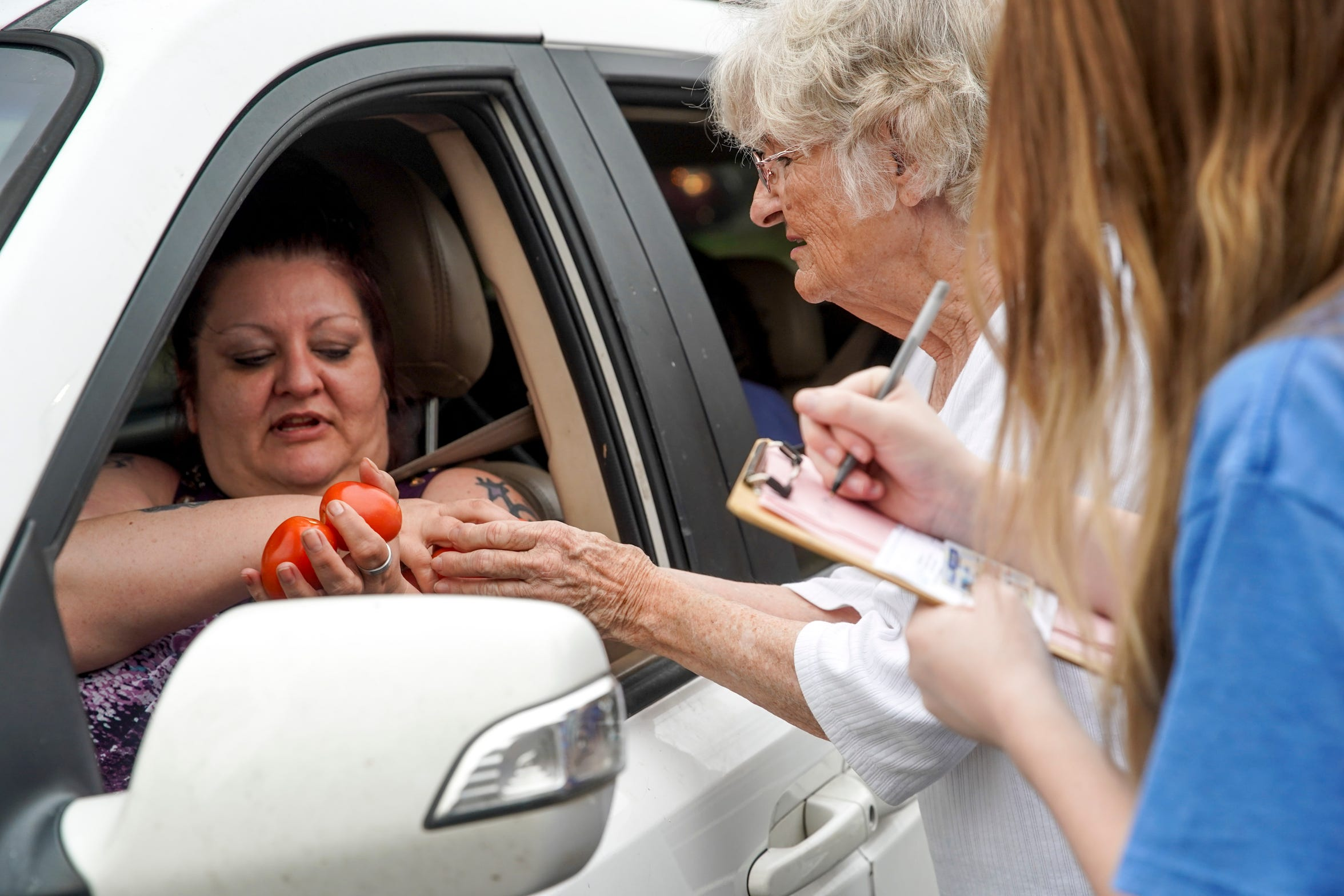 Molly Cook shares a handful of tomatoes with Urban Ministries clients at Madison Street United Methodist Church in Clarksville, Tenn., on Friday, March 27, 2020.