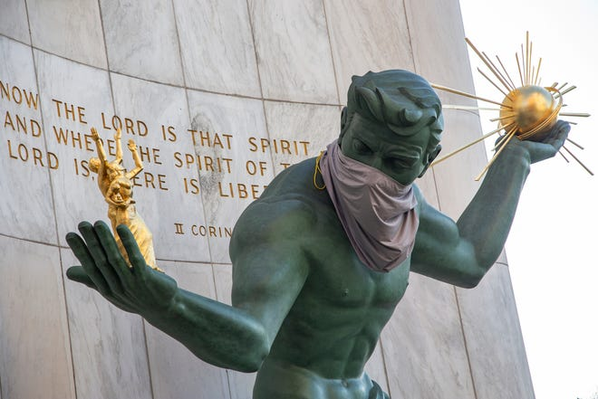 The Spirit of Detroit statue dons a makeshift mask Monday, April 6, 2020, as metro Detroiters hunker down during a stay-at-home mandate due to the novel coronavirus.