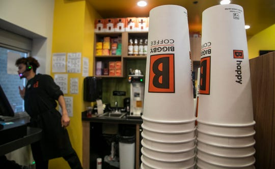 Biggby Coffee barista Andre Morgan, 21, of E. Lansing checks on drive-thru customers Tuesday, Feb. 25, 2020 at the Biggby Coffee location on W. Grand River Ave. in East Lansing.