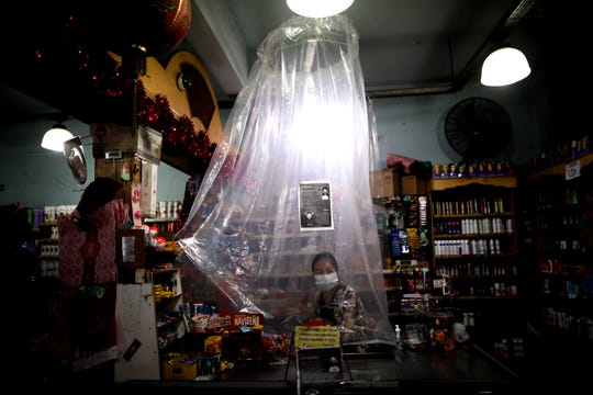 In this March 16, 2020, file photo, supermarket cashier waits for costumers behind a makeshift plastic curtain as a precaution against the spread of the new coronavirus, in Buenos Aires, Argentina.