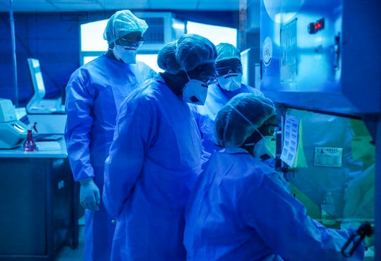 Laboratory technicians, seen behind a blue-tinted window, work on testing patient samples for the new coronavirus that causes COVID-19, at the Pathologists Lancet Kenya laboratory in Nairobi, Kenya on Sunday.