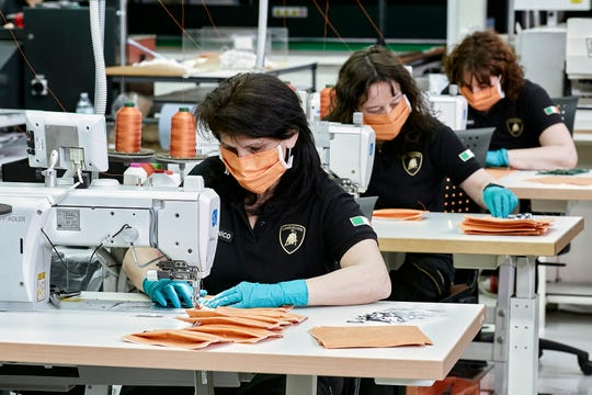 In this photo released on Tuesday, March 31, 2020, Automobili Lamborghini workers produce sanitary masks, at the Sant'Agata Bolognese factory, Italy. Lamborghini converted part of its St. Agata Bolognese plant to produce medical face masks to be delivered to the Bologna's St. Orsola hospital. The new coronavirus causes mild or moderate symptoms for most people, but for some, especially older adults and people with existing health problems, it can cause more severe illness or death. (Automobili Lamborghini via AP)