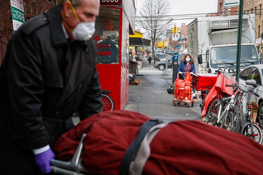Funeral director Tom Cheeseman retrieves a body on a house call, Friday, April 3, 2020, in the Brooklyn borough of New York. Cheeseman is picking up as many as 10 bodies per day. Most bodies come from homes and hospitals.