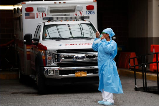 An emergency room nurse dons her face protectors after taking a break Sunday in a driveway for ambulances and emergency medical services vehicles outside Brooklyn Hospital Center's emergency room.