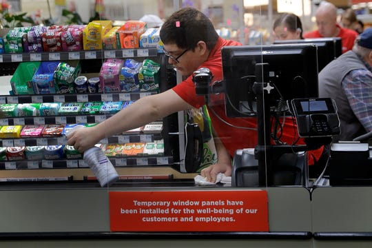 In this March 26, 2020, file photo, Garrett Ward sprays disinfectant on a conveyor belt between checking out shoppers behind a plexiglass panel at a Hy-Vee grocery store in Overland Park, Kan.