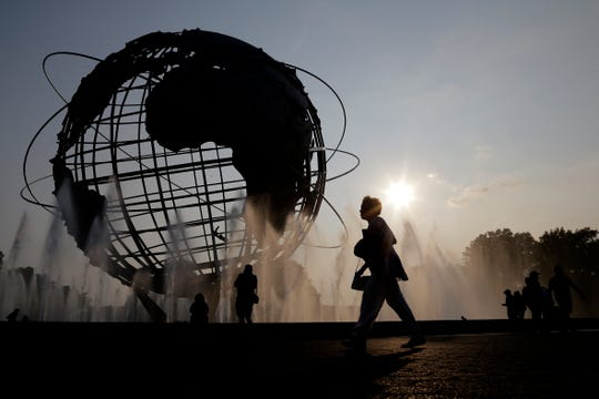 In this Aug. 27, 2018, file photo, a woman walks by a fountain outside of the Billie Jean King Tennis National Center during the first round of the U.S. Open tennis tournament in New York.