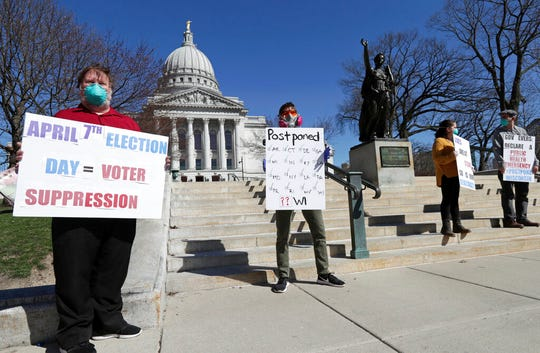 A group with C.O.V.I.D., Citizens Outraged Voters in Danger, including, from left, Ron Rosenberry Chase and Jim O'Donnell, protest while wearing masks outside the State Capitol during a special session regarding the spring election in Madison, Wis., Saturday, April 4, 2020. Wisconsin Republicans say they will ask the U.S. Supreme Court to block extended absentee voting in Tuesday's primary, despite public health fears about in-person voting amid the coronavirus pandemic.