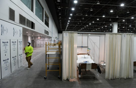 A worker installing a wall, left, with a finished room example, at right, at the field hospital at the TCF Center in Detroit on April 6, 2020.
