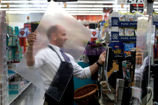 In this March 26, 2020, file photo, Dave Herrick installs a plexiglass panel at a checkout lane at a Hy-Vee grocery store in Overland Park, Kan.