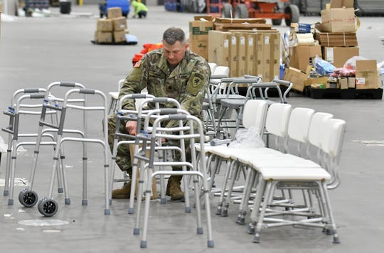 A member of the Michigan National Guard assembles walkers at the field hospital for non-critical COVID-19 patients at the TCF Center in Detroit on April 6, 2020.