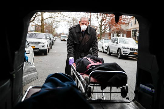 "Funeral director Tom Cheeseman loads a body into his van after making a house call, Friday, April 3, 2020, in the Brooklyn borough of New York. The Associated Press spent a day on the road with Cheeseman, who is overwhelmed by demand due to the coronavirus outbreak. Cheeseman is picking up as many as 10 bodies per day. Most bodies come from homes and hospitals. ""We took a sworn oath to protect the dead, this is what we do,"" he said."