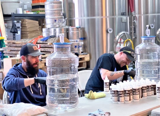 Kevin Collins, left, owner of Cider Creek Hard Cider in Canisteo, and Justin Recktenwald, owner of Wild Brute Winery in Arkport, work on bottling hand sanitizer made from unsold alcoholic beverages.