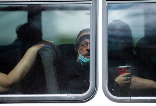 A resident of Washington Nursing Center at 603 E. National Hwy in Washington, Ind., watches the ruckus happening outside the bus he was riding in Monday afternoon, April 6, 2020. Protesters were blocking the bus from leaving the facility to transfer the residents to another Chosen Healthcare facility in Hanover, Ind. The company allegedly decided to turn the Washington, Ind., facility into a COVID-19 hospital.