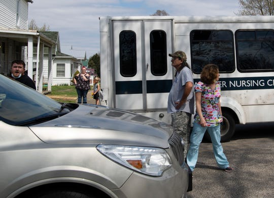 Jesse Martindale, second right, is blocked by a caregiver with Washington Nursing Center at 603 E. National Hwy in Washington, Ind., as he tries to stop a bus leaving the facility Monday afternoon, April 6, 2020. Protesters were unhappy about the surprise transferring of family and friends from the facility. The owner of the company, Chosen Healthcare, was attempting to move the longtime residents to different facilities it owns in Indiana so they could allegedly turn the facility into a COVID-19 hospital.