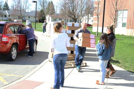 Volunteers pass out meal boxes at Fremont Middle School on Monday morning.